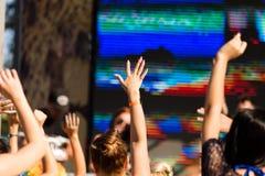 女孩的手上升了在音乐会 库存图片