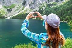 女孩的手做心脏标志象和山背景 免版税图库摄影