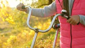 女孩的手拿着弯曲的自行车把手 特写镜头 女孩在秋天走在有自行车的公园 股票录像