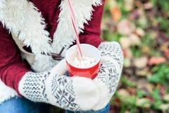 女孩的手拿着杯子热的饮料和坐草 库存照片