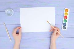 女孩的手有一把油漆刷的有一张白色空白的纸片的在紫罗兰色木背景的和水彩油漆 免版税库存图片