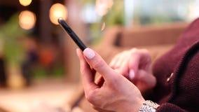 女孩的手键入在智能手机屏幕,特写镜头上的一则流动消息 女孩的手指有修指甲屏幕的 股票录像