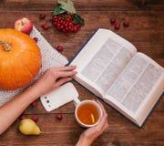 女孩的手顶视图在桌、南瓜、苹果和书,在木桌上的电话上的 免版税库存图片