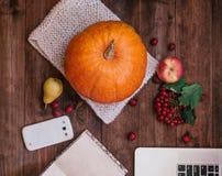 女孩的手顶视图在桌、南瓜、苹果和书,在木桌上的电话上的 免版税图库摄影