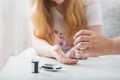 女孩的测量的血糖水平有Glucometer的 图库摄影
