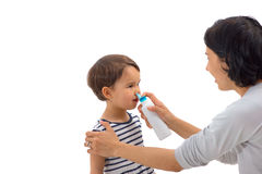 女孩的父母的手应用被隔绝的鼻孔喷射 图库摄影