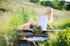 女孩的白色sundress和有花花圈的在手s上 免版税库存照片