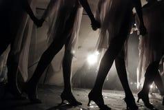 女孩的腿剪影跳舞在阶段的在音乐会期间 免版税库存照片