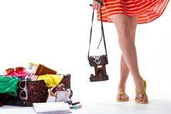 女孩的腿和被过度充填的手提箱 免版税库存照片