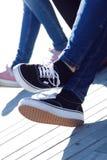 女孩的腿牛仔裤和运动鞋的 免版税库存照片