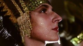 女孩的面孔的特写镜头在时装的 女孩有一件时髦的礼服和一样美丽的头饰与衣服饰物之小金属片 股票录像
