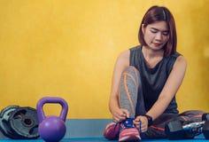 女孩的鞋带的在健身房的手和运动鞋准备好 免版税图库摄影