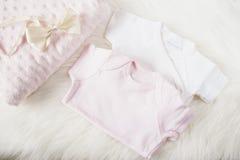 女孩的婴孩衣裳 婴孩连衫裤、连裤外衣、弓发带和桃红色尿布 在一张白色毛皮地毯上 新出生的婴孩概念 婴孩 免版税库存图片