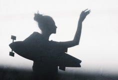 女孩的阴影照片有滑板的 免版税图库摄影