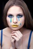 女孩的黄色蓝色泪花 库存照片