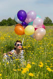 女孩的Pin有五颜六色的气球的一个用花装饰的草甸的 免版税库存照片