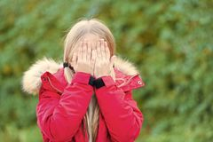 女孩皮面孔用手在田园诗秋天天 库存照片