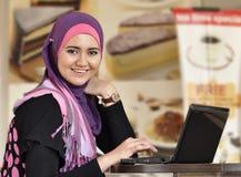 女孩相当膝上型计算机穆斯林 免版税库存照片