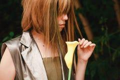 女孩看一朵花 库存图片