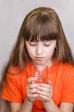 女孩看一杯水 库存图片