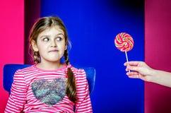女孩看与兴趣为她被提供的糖果 免版税库存图片