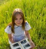 女孩看与照片的一个册页 免版税库存照片