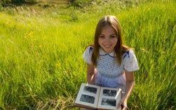 女孩看与照片的一个册页 免版税库存图片