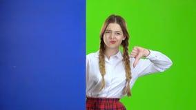 女孩看从一个蓝色委员会的后面并且显示拇指下来 绿色屏幕 股票录像