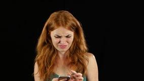 女孩看在她的电话的照片 黑色背景 股票录像