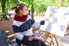 女孩看在画架的背景的一根枝杈 库存照片