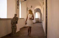 女孩看在老城堡的一个雕塑 库存图片