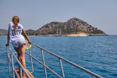 女孩看往港口,站立在弓游览小船 免版税库存照片