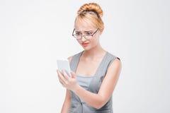 女孩看看充满憎恶和反感的电话 图库摄影