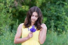 女孩看野花的花束14岁 免版税库存照片