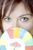 女孩看从一个大棒棒糖的后面 免版税库存照片