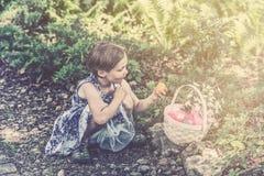 女孩看从减速火箭她的篮子的一个复活节彩蛋- 库存照片