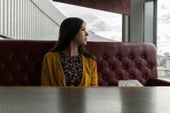 女孩看staringly窗口并且坐在咖啡馆的一个红色沙发 女孩等待她的顺序 免版税库存照片