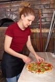 女孩真正的薄饼在比萨店 免版税库存图片