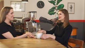 女孩研究一台膝上型计算机在咖啡馆,Barista给她一杯咖啡 影视素材
