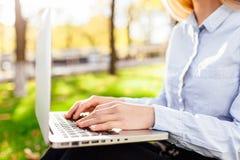 女孩研究膝上型计算机的,手在公园键入文本,特写镜头 免版税库存图片