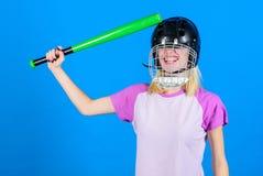 女孩确信的俏丽的白肤金发的穿戴棒球盔甲和举行棒在蓝色背景 棒球女性球员概念 准备好 图库摄影