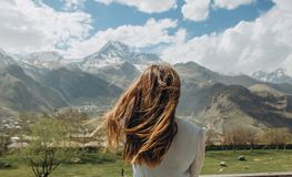 女孩礼服在夏天后看山雪峰顶 库存照片