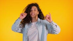 女孩移动向音乐节奏  与卷发跳舞的Woamn在黄色背景 女性获得乐趣 她微笑 股票视频
