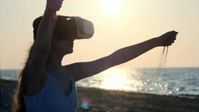 女孩穿戴虚拟现实玻璃, VR耳机 通过您的手指倾吐沙子  坐沙子由 股票录像
