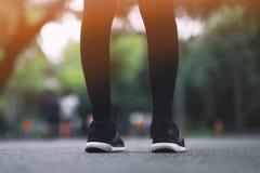 女孩穿黑跑鞋在公园跑 免版税库存图片