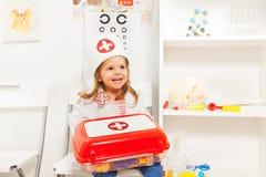 女孩穿戴了象有玩具紧急救护胸口的医生 免版税库存图片