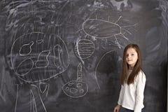女孩突出在黑板 免版税库存照片