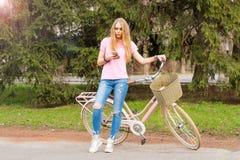 女孩站立与一个手机和一辆自行车在公园 免版税库存图片