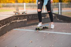 女孩站立与在一个滑板的一只脚在冰鞋公园 免版税库存照片