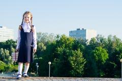 女孩站立与在街道上的课本,在右边那里是题字的一个地方 图库摄影